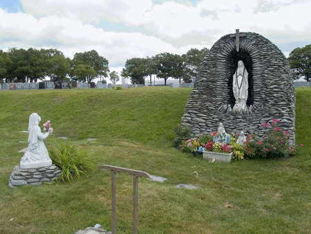 A statue of Our Lady of Lourdes and Bernadette in a rock grotto surrounded by nice flowers.