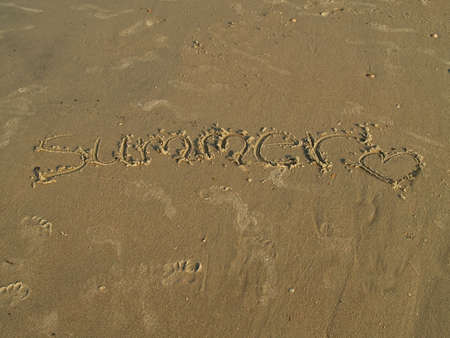 The word Summer, hand drawn in the sand along a beach.