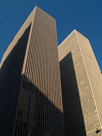 Two tall buildings against a clear blue sky in Manhattan. photo