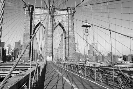 A black and white view of the pedestrian walkway on the Brooklyn Bridge. photo