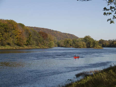 canoe sails down the Delaware River, part of the Delaware National Recreation area between New Jersey and Pennsylvania. Stock Photo