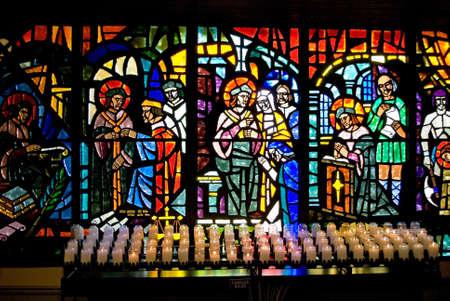 vetrate colorate: Vetrate e le candele votive in una Chiesa cattolica.