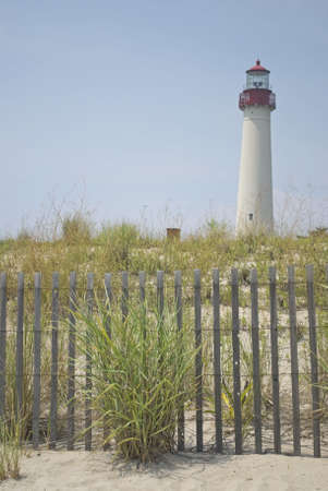 The Cape May Lighthouse with a fence and sand dunes in the foreground. Stock Photo