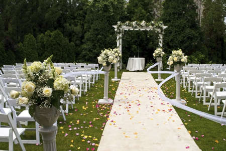 Een witte bruiloft tapijt bedekt met rozenblaadjes en het toneel van een recente buiten tuin ceremonie.