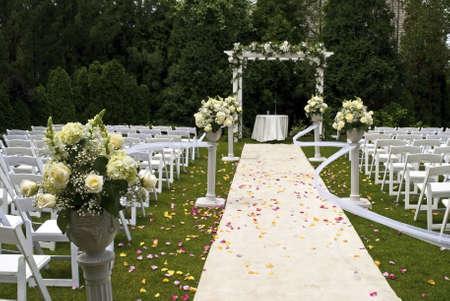Einem weißen Hochzeit-Teppich in rose Blütenblätter und der Szene einer jüngsten outdoor-Garten-Zeremonie der behandelt.