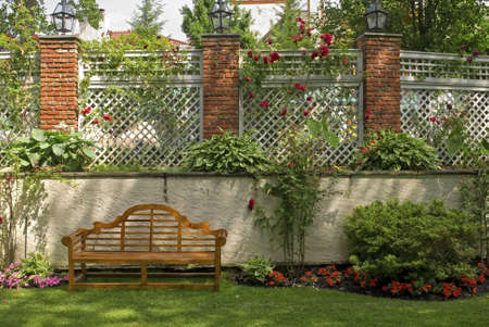 red wall: A garden wall with a trellis and red rose bushes. Stock Photo
