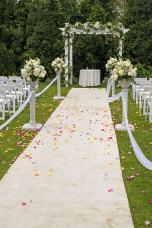 A white wedding carpet covered in rose petals and the scene of a recent outdoor garden ceremony.