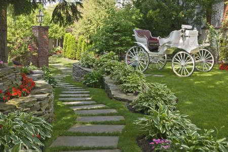 paisajismo: Un carro antiguo en un hermoso jard�n ornamental de verano.