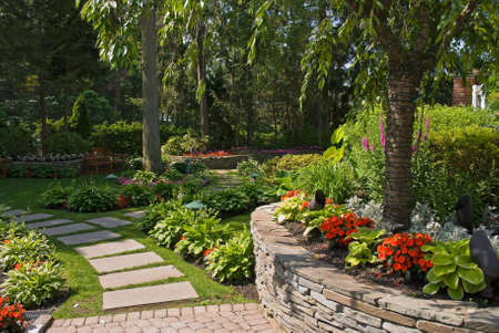 A Summer view of an ornamental garden with a slate pathway and garden wall made out of stone.