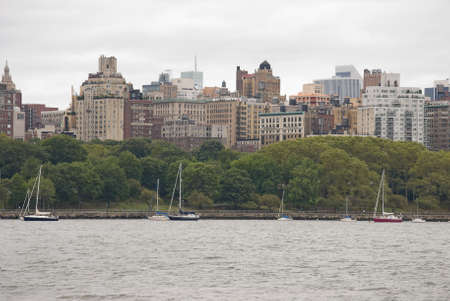 Sailboats along a marina in uptown Manhattan with many buildings in the background. Фото со стока