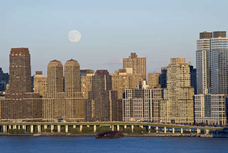 A full moon in daytime rises up over Manhattan as seen from across the Hudson River in New Jersey. photo
