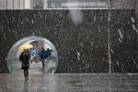 Manhattan - January 7: A woman with an umbrella passes through the Waterfall Park near Rockefeller Center during the snowfall on January 7 2011 in Manhattan.