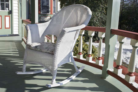 A white wicker rocking chair on a colorful sunny porch. Stock Photo