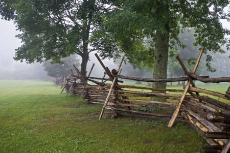 battlefield: A Wooden fence along the open field in Monmouth Battlefield State Park on a foggy Summer morning.  Stock Photo
