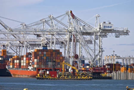 BAYONNE, NJUSA-MARCH 9: Large cranes and a barge full of containers at The Global Terminal & Container Service  on the Hudson River on March 9, 2012 in Bayonne,NJ. The Company is one of the largest on the East Coast for international shipping.