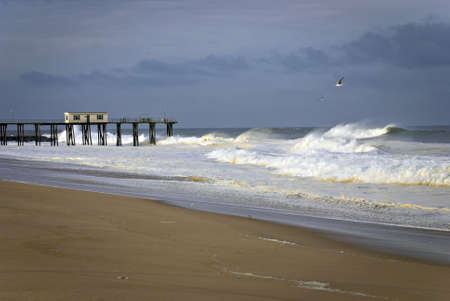 The fishing pier and beach with stormy seas in Belmar, New Jersey. Stok Fotoğraf