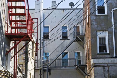 A Courtyard Of Old Brick Apartment Buildings With Electrical Wires Stock Photo