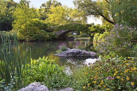 뉴욕시에서 중앙 공원에서 오리 연못과 돌 다리의 여름보기.