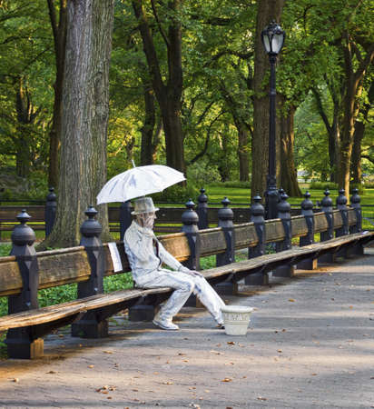 Sitting Mime Central Park  A man in Central Park performs a mime of a statue figure with umbrella seated on a park bench. Editorial