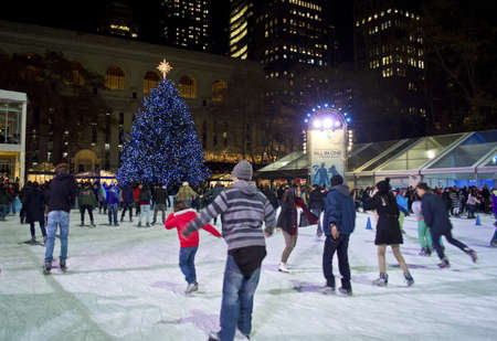 bryant: NEW YORK - NOVEMBER 30: Ice skaters on the rink in Bryant Park near the Christmas tree on November 30, 2012 in  New York City.