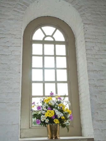 Flowers in Window   A vase of fresh cut flowers in an old church in Colonial Williamsburg, Virginia  photo