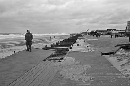 BELMAR, NEW JERSEY/USA  OCTOBER 30: A man stands on the badly damaged boardwalk the day after Hurricane Sandy on October 30 2012 in Belmar, NJ.