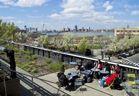 Tourists stop for a brake on The High Line the former raised train tracks now a popular park in New York City. Editorial