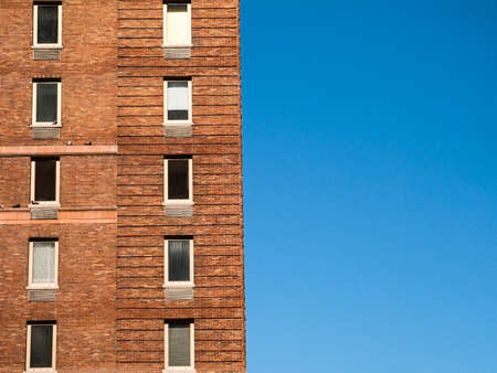 apartment: An old brick apartment building against a blue sky in New York City
