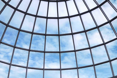grid pattern: A glass dome with a cloudy blue sky on the ceiling of this modern building. Stock Photo