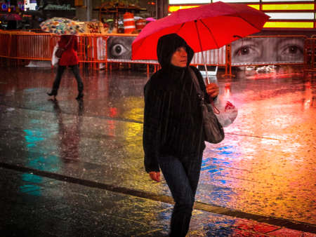 A lady with a red umbrella walks through Times Square on April 16 2014