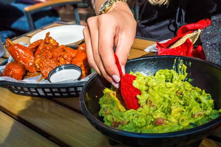 A girl dips into the guacamole with chips along with buffalo wings on the side as appetizers  Banco de Imagens