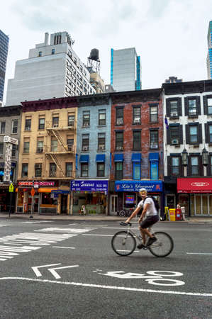 establishments: NEW YORK-JULY 29-A man on bicycle passes along 2nd Avenue on the East Side July 29 2014 in Manhattan  Turtle Bay is a section of the East Side with many small business establishments