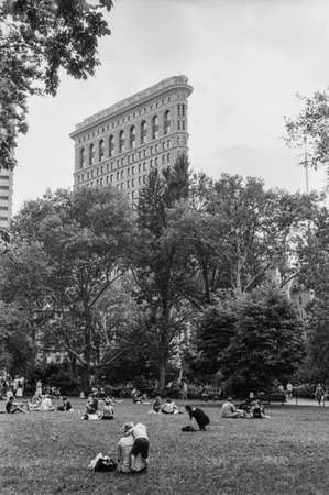 b and w: B W film photograph of people enjoying a relaxing day in Madison Park with the Flatiron Building in the background
