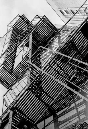 lower east side: A black and white film photograph of a fire escape on a building in the lower East Side of Manhattan