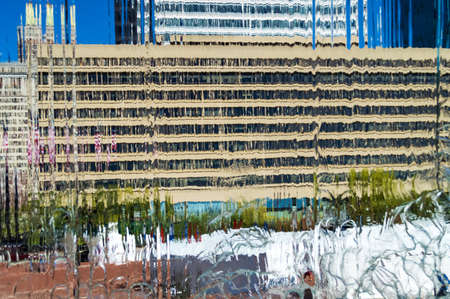 Buildings viewed through waterfall fountain creating an interesting abstract background. Фото со стока