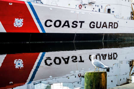 guard ship: BALTIMORE, MARYLAND-SEPTEMBER 28-A seagull on watch near a Coast Guard ship in the Inner Harbor September 28 2014 in Baltimore Maryland.