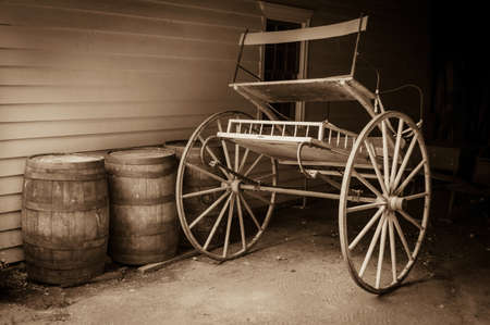 duo tone: An antique 19th century carriage with old barrels and sepia toned. Stock Photo