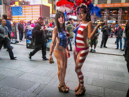 body paint sexy: NEW YORK-OCTOBER 10: Two patriotic ladies in red white and blue looking for tips from tourists with cameras in Times Square on October 10 2014 in Manhattan.