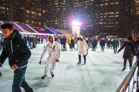 bryant park: NEW YORK-DECEMBER 10: Ice skaters enjoy the falling snow at the Bryant Park skating rink on December 10, 2014 in Manhattan.