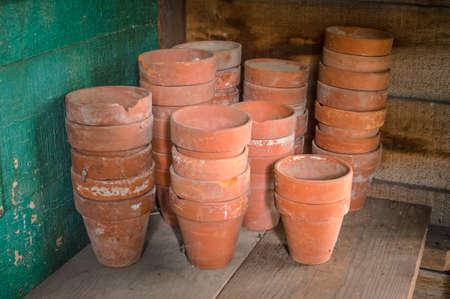 ollas de barro: Las ollas de barro en un estante de madera en un viejo cobertizo. Foto de archivo