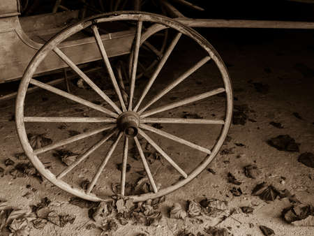 old fashioned sepia: A sepia toned old fashioned cart wheel on rustic floor with leaves.