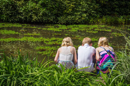 children pond: HAMILTON TOWNSHIP NEW JERSEY  MAY 9: Three children look into a pond at the Azalea Festival on May 9 2015 in Hamilton Township New Jersey. Editorial