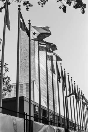 united nations: New York, NY, USA - October 23, 2015: A black and white film photograph of the United Nations building surrounded by the different flags of the world. Editorial