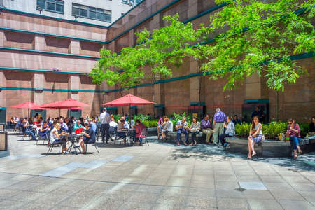 NEW YORK-JUNE 9: People relaxing in a city courtyard on the East side to have their lunch on June 9 2015 in New York City.