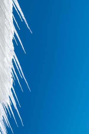 solid blue background: Icicles contrasted against a solid blue sky background. Stock Photo