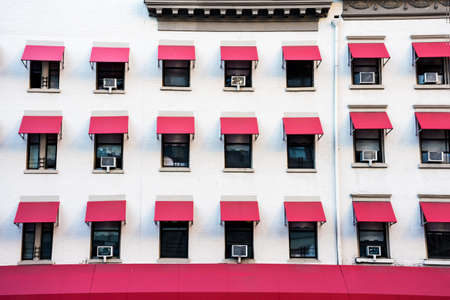 A white building with repetitive pink window shades in Manhattan.