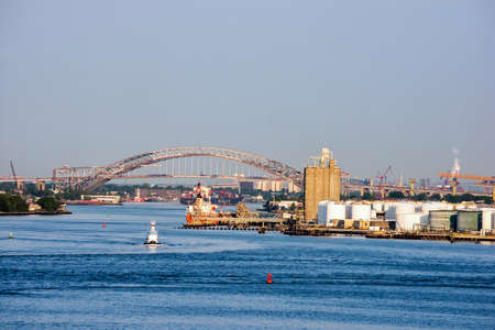 industry architecture: BAYONNE, NEW JERSEY- MAY 29 - A view of the Bayonne Bridge renovation progress from the Hudson Bay on May 29 2016 in New Jersey.