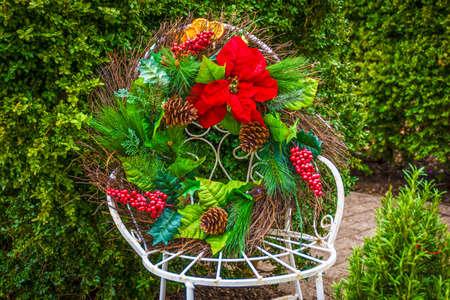 A Christmas wreath with poinsettia on an antique white iron chair. Stock Photo