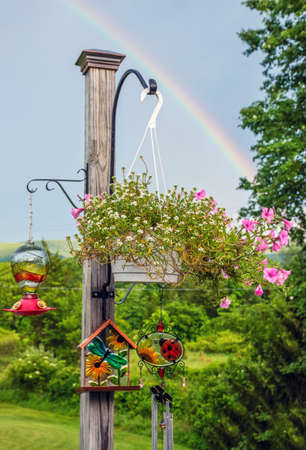 An outdoor plant post with hanging plants and rainbow in the sky.