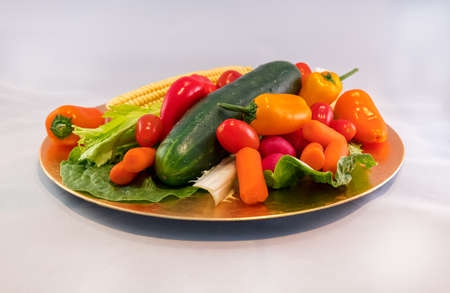 A platter of fresh vegetables with a neutral white background.